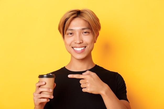 Nahaufnahme des zufriedenen hübschen asiatischen blonden kerls, der entzückt lächelt und finger auf köstliche tasse kaffee zeigt, über gelber wand stehend