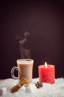 Nahaufnahme des zusammengesetzten bildes von heißer schokolade und kerze