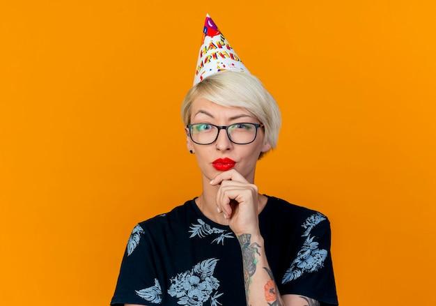Nahaufnahme des zweifelhaften jungen blonden partygirls, das brille und geburtstagskappe betrachtet, die kamera berührendes kinn lokalisiert auf orange hintergrund mit kopienraum betrachten