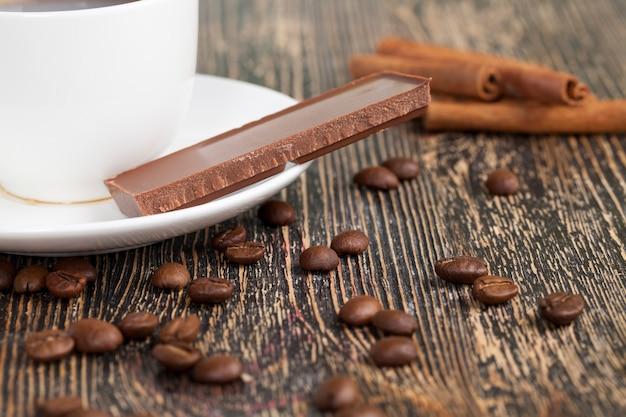 Nahaufnahme dessert aus kaffee- und kakaobonbons, süße schokolade aus kakao und zucker mit heißem kaffee, kaffee mit einer tasse und milchschokolade