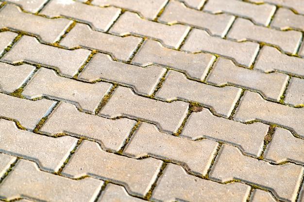 Nahaufnahme detail der grauen betonhofpflasterplatten.