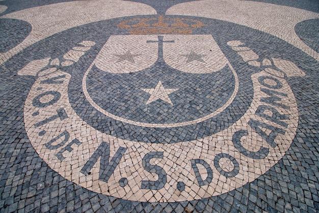 Nahaufnahme detail des wappens der plaza of carmo von faro auf kopfsteinpflaster in portugal.