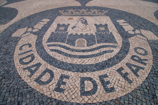 Nahaufnahme detail des wappens der stadt faro auf kopfsteinpflaster in portugal.