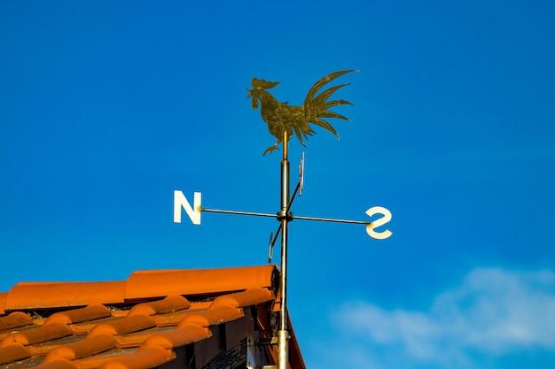 Nahaufnahme detailansicht der wetterfahne auf dem dach des hauses.