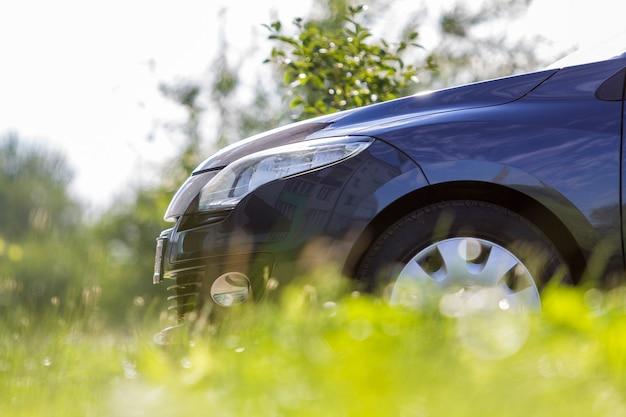 Nahaufnahme detailfront des modernen neuen glänzenden leeren schwarzen autos, das außerhalb der straße in hohem gras an hellem sonnigem sommertag auf unscharfem grünem baumhintergrund geparkt wird. verkehrs-, umweltverschmutzungs- und ökologiekonzept.