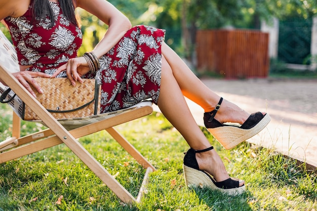Nahaufnahme details beine tragen keile sandale schuhe, schuhe, stilvolle schöne frau sitzen im liegestuhl im tropischen stil outfit, sommer modetrend, stroh handtasche, accessoires, urlaub