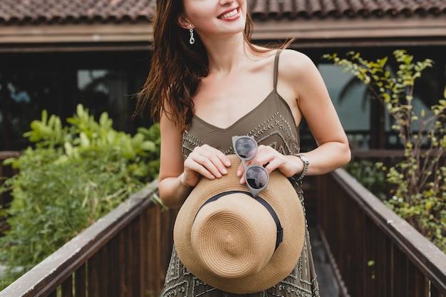Nahaufnahme details hände halten strohhut und sonnenbrille, stilvolle accessoires, junge attraktive frau in elegantem kleid, sommerstil, modetrend, urlaub, posiert auf tropische villa, lächelnd, glücklich
