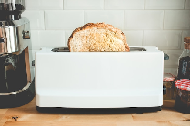 Nahaufnahme, die brot mit toaster auf gegenküchenküche am morgen kocht