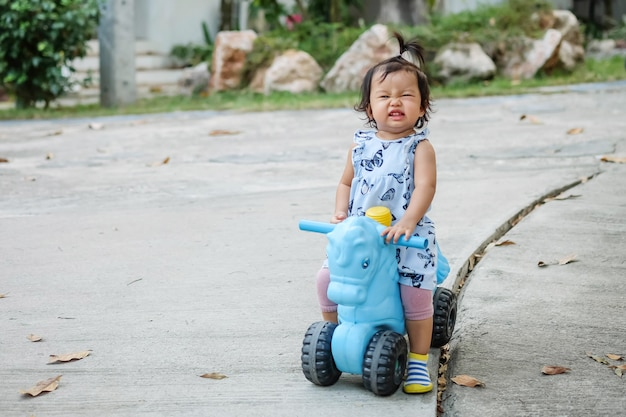 Nahaufnahme, die ein kleines mädchen ein fahrradspielzeug für kind mit glücklichem gesicht auf zementboden im park fährt