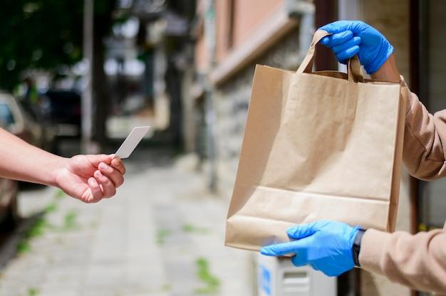 Nahaufnahme, die in papiertüte zum kunden übergibt