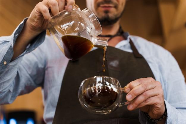 Nahaufnahme, die kaffee in der doppelten glasschale im café durch hübschen bärtigen barista gießt
