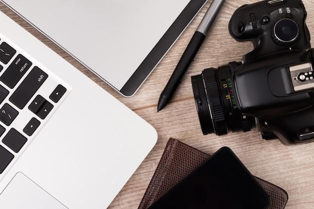 Nahaufnahme draufsicht des fotografen des grafikdesignerarbeitsplatzes. laptop, grafiktablett, telefon und fotokamera auf holztisch.