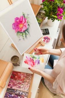 Nahaufnahme draufsicht mädchen künstler wählt trockene pastellfarben zum zeichnen der rosa hagebuttenblume, die am schreibtisch mit palette und staffelei und einem strauß hagebutten sitzt. kreativität und hobbykonzept