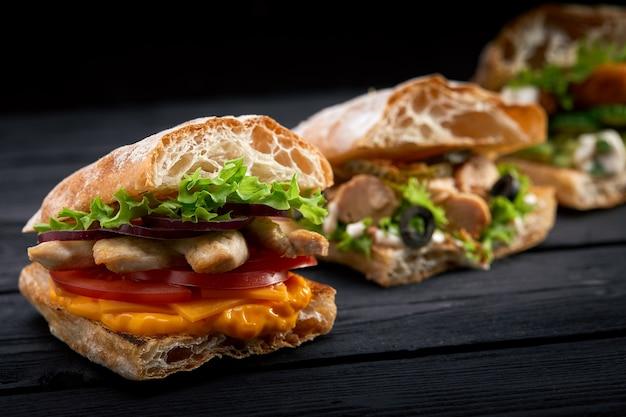 Nahaufnahme drei verschiedene appetitliche sandwiches oder burger auf hölzernem hintergrund