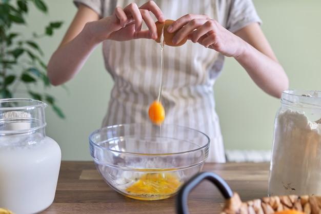 Nahaufnahme, ein ei in eine schüssel zu brechen, teig für pfannkuchen zuzubereiten.