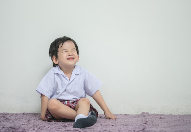 Nahaufnahme ein kleinkind in der studentenuniform mit lächelngesicht sitzen auf dem gemaserten teppich und weißer wand