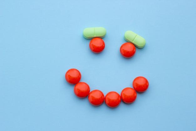 Nahaufnahme, ein lächeln von den orange und grünen pillen, konzeptgesundheit