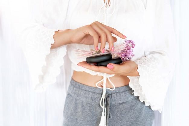 Nahaufnahme: ein mädchen mit einer schönen zarten rosa maniküre hält zwei schwarze steine für kuranwendungen und blumen. spa und hautpflege, massage.