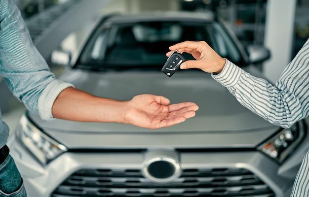 Nahaufnahme ein mann kauft ein auto und erhält schlüssel vom verkäufer.