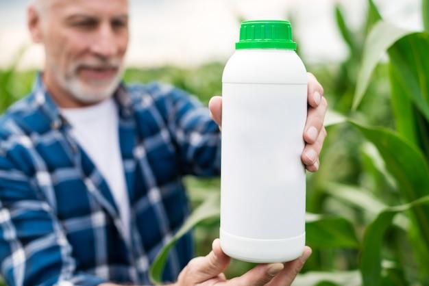 Nahaufnahme eine flasche mit mineraldüngern in der hand des mitte gealterten landwirts. attrappe, lehrmodell, simulation