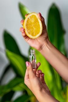 Nahaufnahme: eine weibliche hand drückt saft aus einer zitrone in eine glasflasche. die naturkosmetik