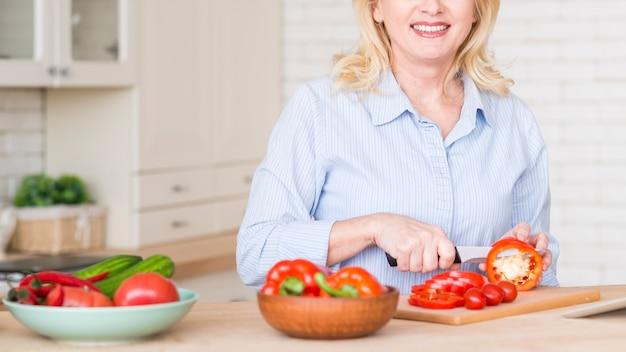 Nahaufnahme einer älteren frau, die den roten grünen pfeffer mit messer auf tabelle in der küche schneidet
