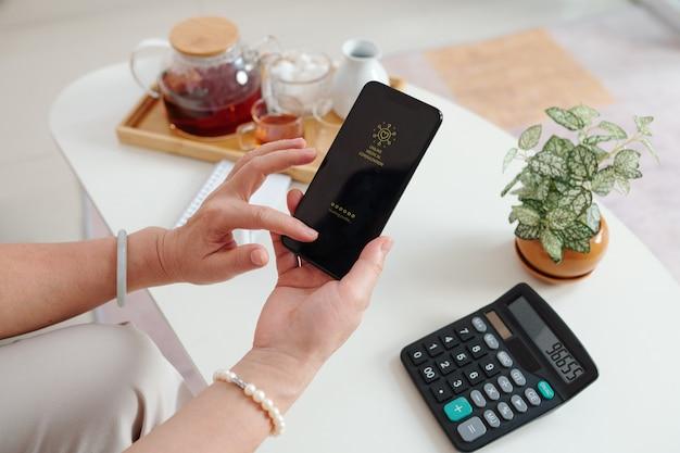 Nahaufnahme einer älteren frau, die eine online-app für medizinische beratung auf dem smartphone verwendet, um mit ihrem arzt zu kommunizieren