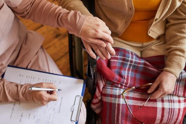 Nahaufnahme einer älteren frau, die während der therapiesitzung im altersheim händchen mit einer krankenschwester hält