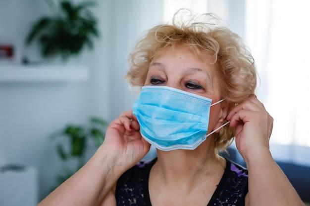 Nahaufnahme einer älteren frau mit einer medizinischen maske im gesicht. das globale problem des coronavirus.