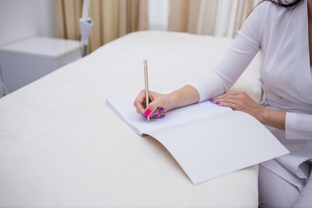 Nahaufnahme einer ärztin, die in ein notizbuch schreibt