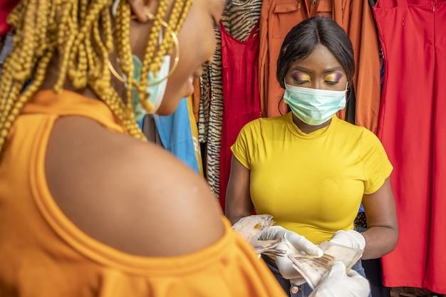 Nahaufnahme einer afrikanischen frau mit latexhandschuhen und einer gesichtsmaske, die mit bargeld an einem geschäft zahlt