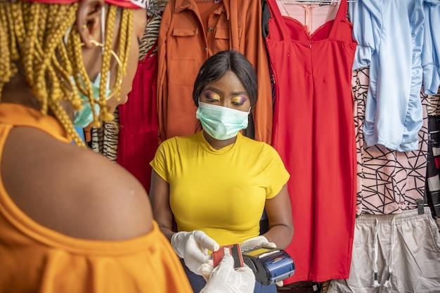 Nahaufnahme einer afrikanischen frau mit latexhandschuhen und einer gesichtsmaske, die mit einer kreditkarte an einem geschäft zahlt