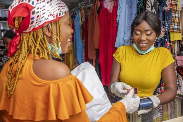 Nahaufnahme einer afrikanischen frau mit latexhandschuhen und einer gesichtsmaske, die mit einer kreditkarte in einem geschäft bezahlt