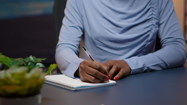 Nahaufnahme einer afrikanischen geschäftsfrau, die eine liste von aufgaben für ein geschäftsprojekt in einem notebook schreibt, das am schreibtisch im wohnzimmer sitzt und überstunden macht. schwarzer freiberufler respektiert die frist, die spät in der nacht studiert