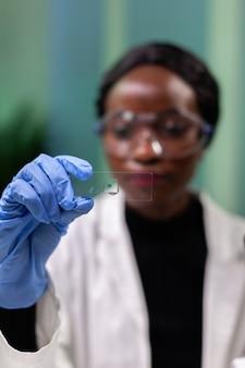 Nahaufnahme einer afroamerikanischen mikrobiologin, die eine grüne blattprobe betrachtet, die an medizinischen experimenten im mikrobiologischen krankenhauslabor arbeitet. botaniker, der gentechnisch veränderte pflanzen analysiert