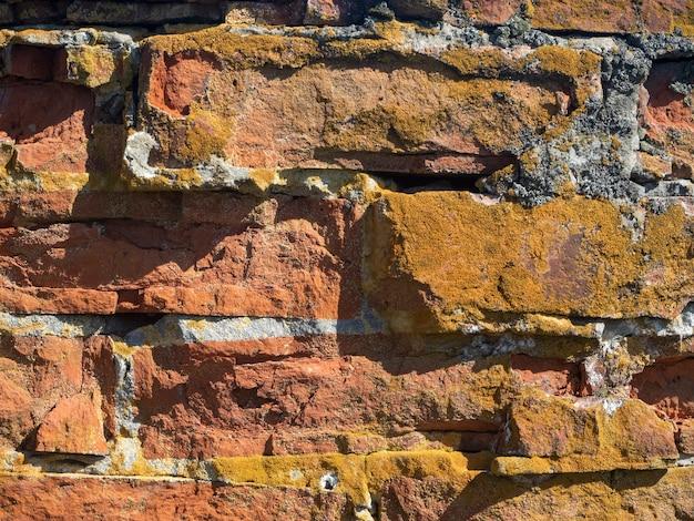 Nahaufnahme einer alten gebrochenen roten backsteinmauer.