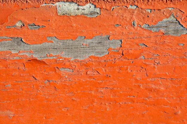 Nahaufnahme einer alten orangefarbenen lackstruktur, die sich vom holzbretthintergrund ablöst