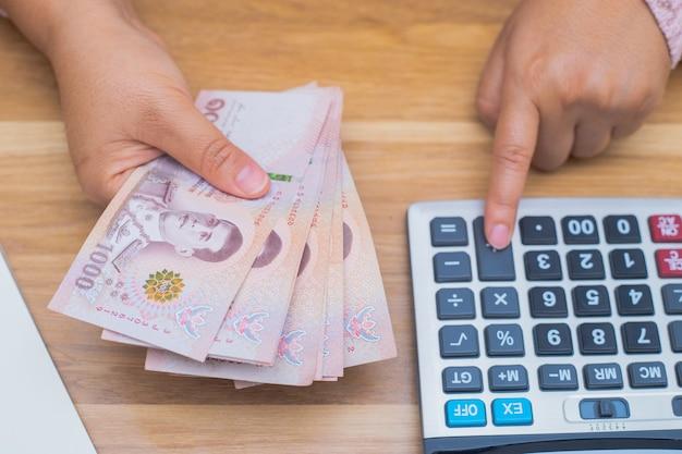 Nahaufnahme einer asiatischen frau mit taschenrechner, die geld zählt. frau berechnet die ausgaben zu hause.