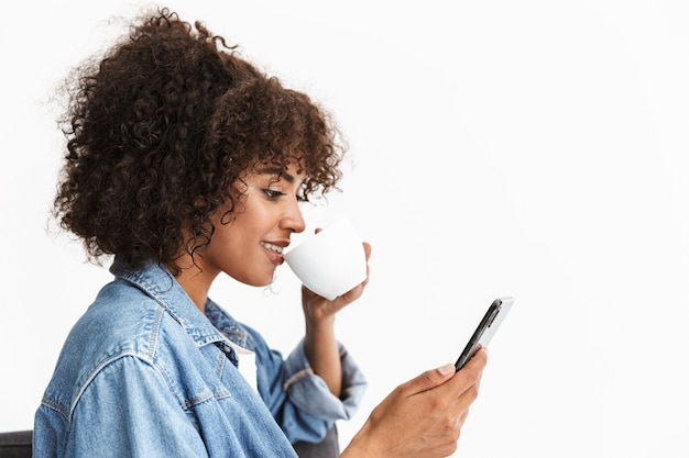Nahaufnahme einer attraktiven jungen frau in denim, die auf einem stuhl sitzt, isoliert über der weißen wand, mit dem handy, während sie kaffee trinkt