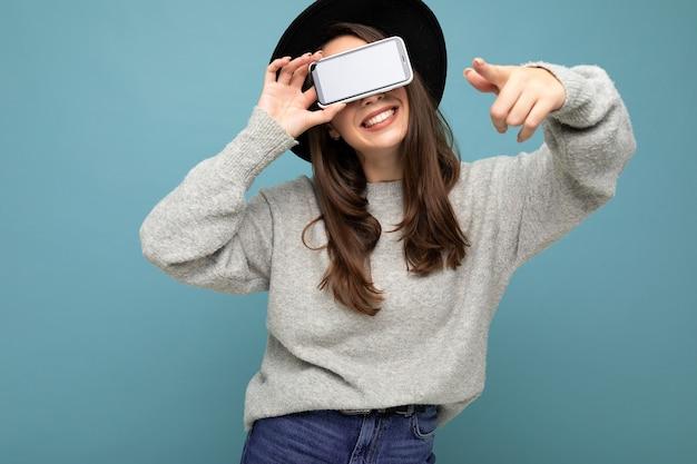 Nahaufnahme einer attraktiven jungen glücklichen frau mit schwarzem hut und grauem pullover, die spaß beim halten des telefons hat