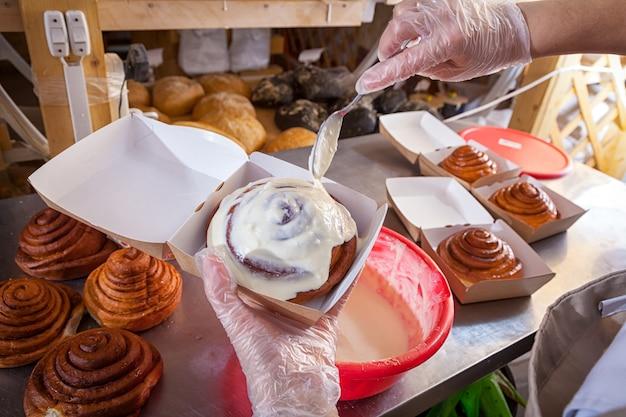 Nahaufnahme einer bäckerin, die creme auf einem brötchen verputzt, im hintergrund ein tisch mit frischen zimtschnecken