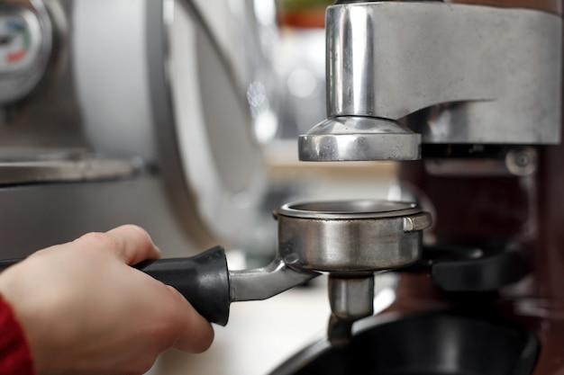 Nahaufnahme einer barista hand, die gemahlenen kaffee in einer halterung für das kochen in einer kaffeemaschine aufhebt
