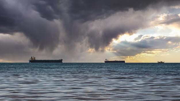 Nahaufnahme einer bewölkten seelandschaft und eines hellen sonnenuntergangs. blaues meer, gewitterwolken mit sonnenstrahlen über dem horizont und mehrere frachtschiffe.