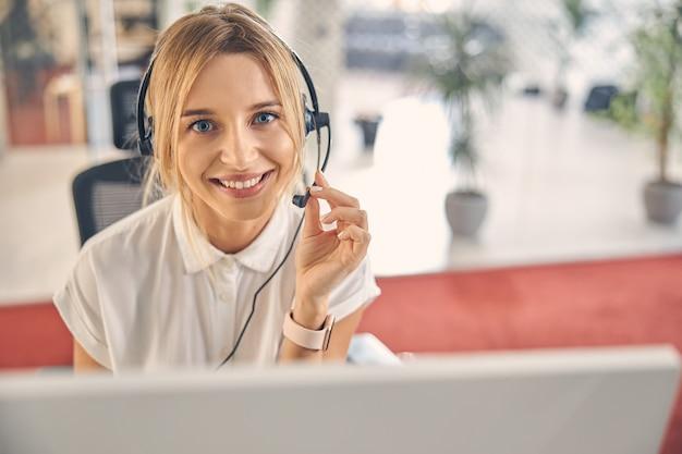 Nahaufnahme einer charmanten arbeiterin, die lächelt, während sie das headset-mikrofon berührt