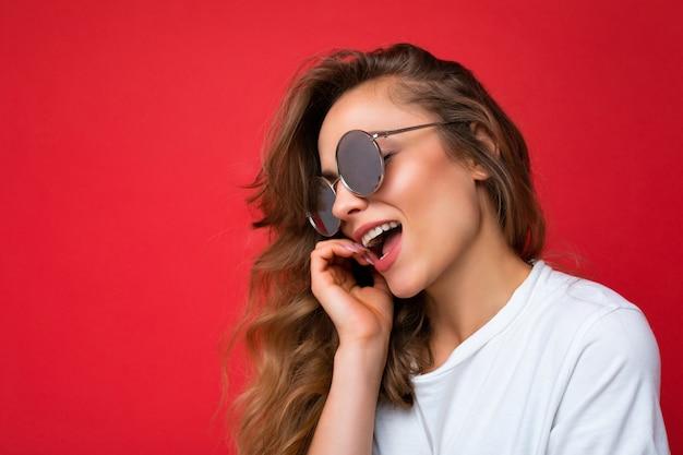 Nahaufnahme einer charmanten, glücklichen jungen dunkelblonden, lockigen frau, die über einer roten hintergrundwand isoliert ist und ein lässiges weißes t-shirt und eine stilvolle sonnenbrille trägt, die zur seite schaut.