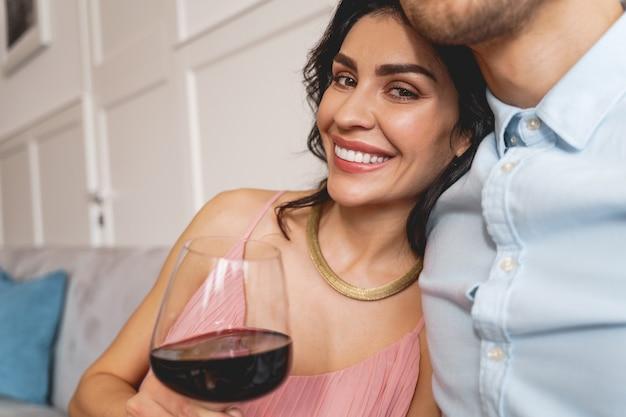 Nahaufnahme einer charmanten jungen frau, die ein glas wein hält und die gesellschaft eines freundes genießt?