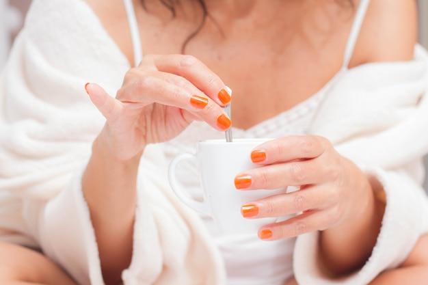 Nahaufnahme einer dame, die den morgenkaffee hält