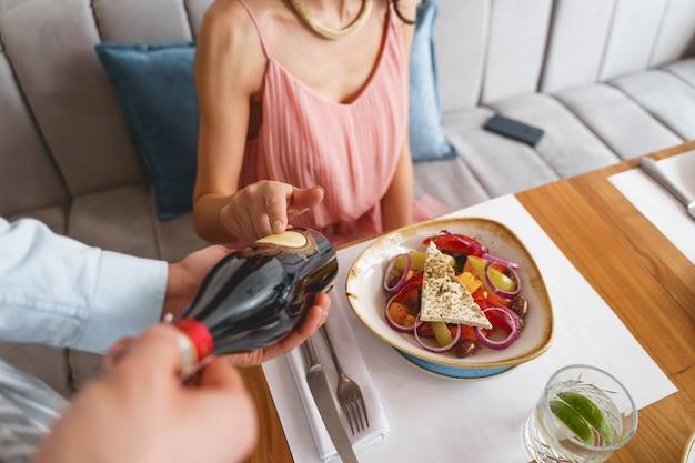Nahaufnahme einer dame, die mit leckerem essen am tisch sitzt, während die café-arbeiterin eine flasche alkoholisches getränk hält?