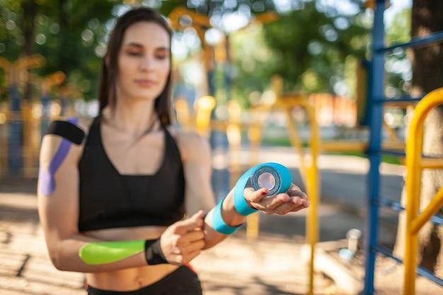 Nahaufnahme einer defokussierten frau, die bunte rollen elastischer kinesiologiebänder hält. selektiver fokus der rehabilitationsbehandlung in den händen junger sportlerinnen mit schwarzer sportbekleidung.