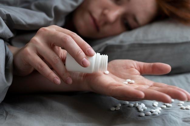 Nahaufnahme einer depressiven frau mit pillen